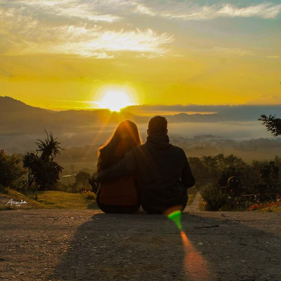 Zwei Personen schauen den Sonnenaufgang