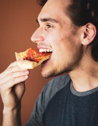 Ein Stück Pizza Margherita essen