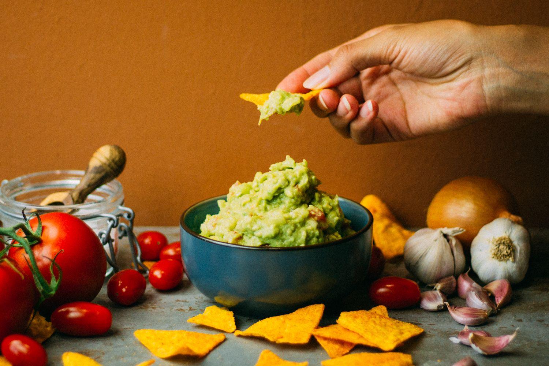 Mit einem Tortilla-Chip etwas von der leckeren Guacamole nehmen.